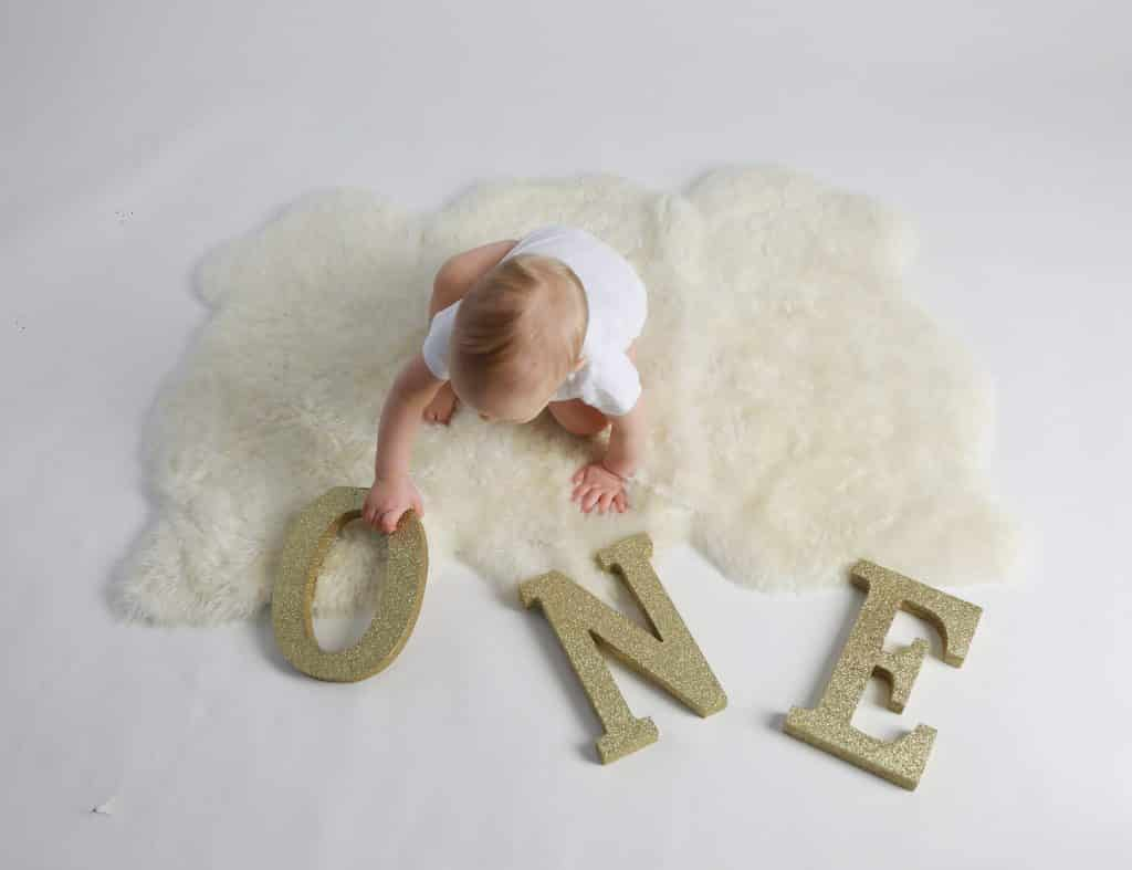 One year boy on white fur wearing a white one piece and touching the gold letter O