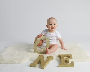 Baby Boy in white onsie with gold letter s that spell one, on a white back ground andsitting on white fur holding the O