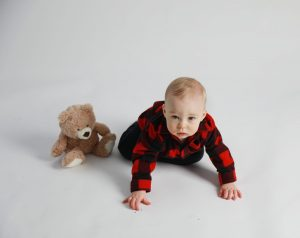 One year boy with red and black plaid sweater and teddy bear crawling to the camera