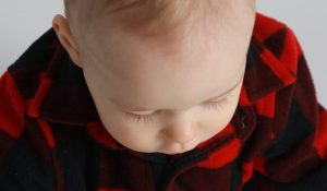 One year boy in plaid sweater looking down showing off his eye lashes