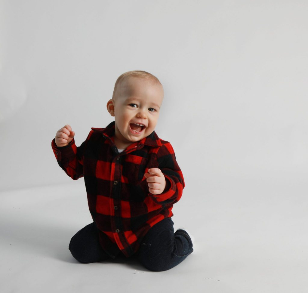 One year boy in plaid sweater and jeans on a white background on his knees bouncing with excitement, hands in the air