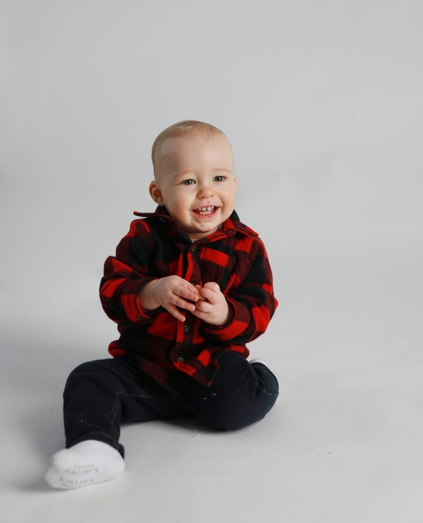 One Year boy sitting on a white background with a plaid sweater and jeans