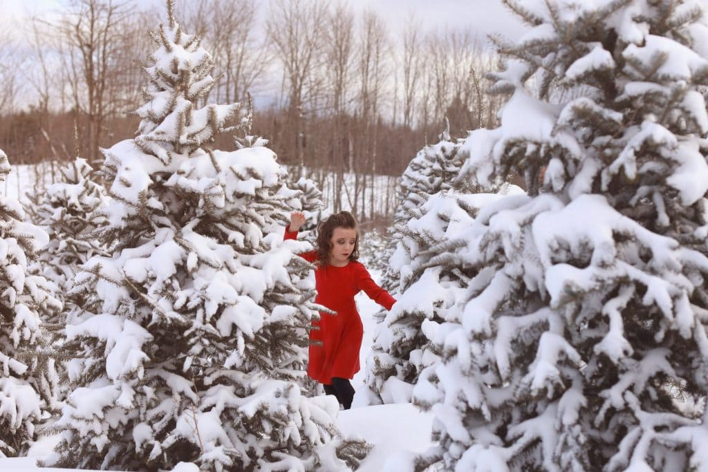 snow covered trees, tree farm, young girl, red dress, almost falling, hands in the air, mouth open, curly hair, hair half up and half down