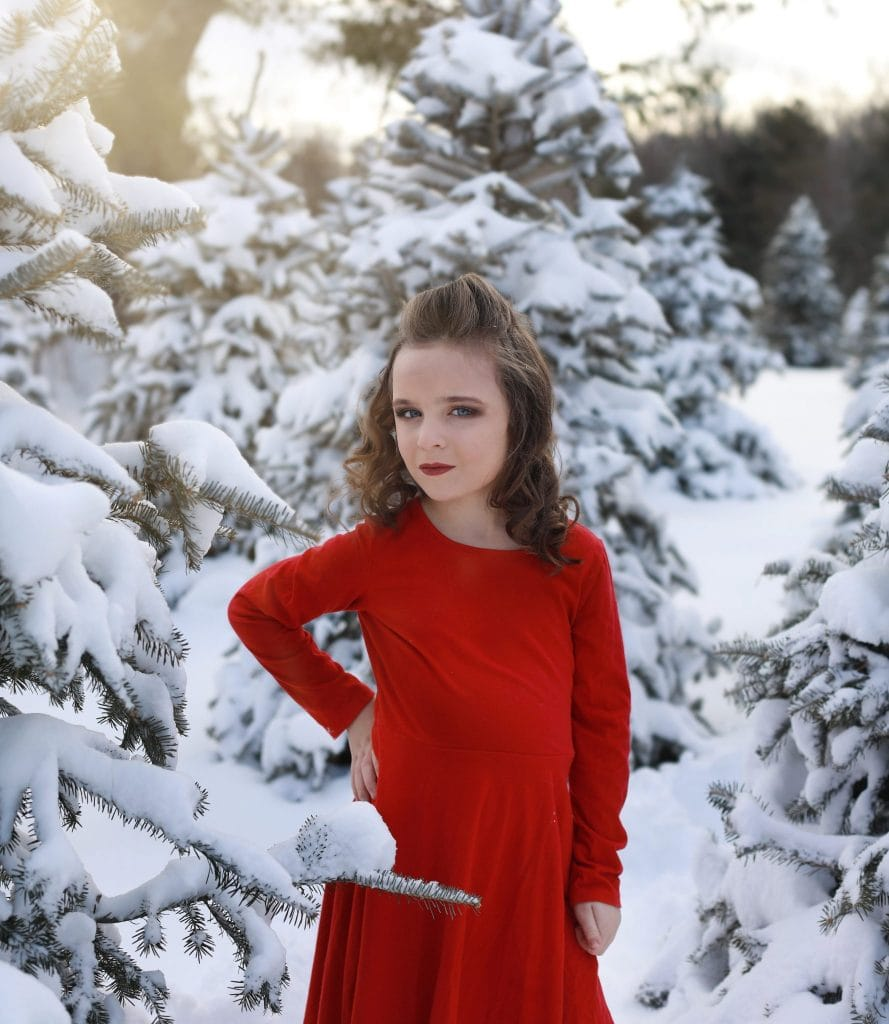 Young girl red dress, curly hair, hair half up and half down, red dress, hand on her hip, looking at the camera, tree farm, snow covered trees, smiling