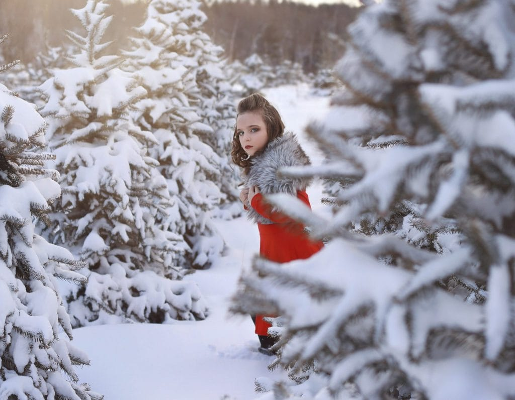 young girl running, curly hair, red dress, grey faux fur, looking sideways to the camera, tree farm, snow covered trees, winter, curly hair half up and half down
