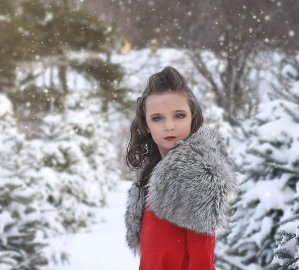 young girl, curly hair, red dress, standing sideways, looking at the camera, tree farm, snow covered trees, snowing
