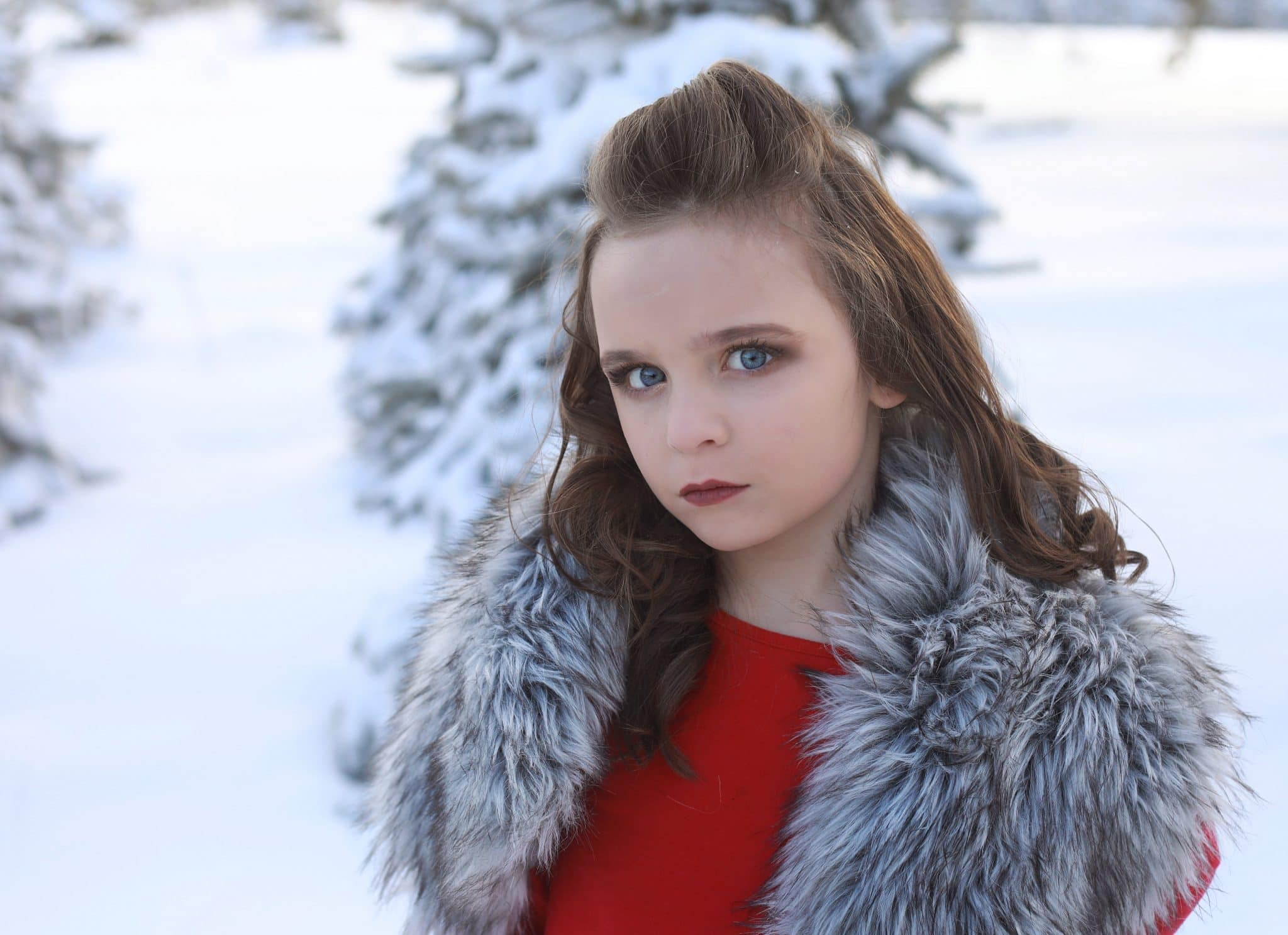 young girl, small smirk, red dress, tree farm covered in white snow, grey faux fur on shoulders