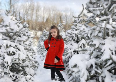 young girl, red coat, looking at the camera, hand on her hip, curly hair, black boots, tree farm, snow covered trees, winter,