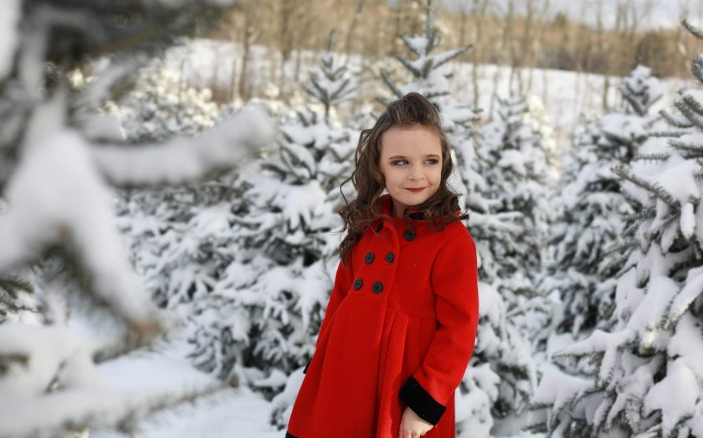 young girl, red dress, looking at mother, tree farm, snow covered trees, winter, red coat, curly hair, smiling.