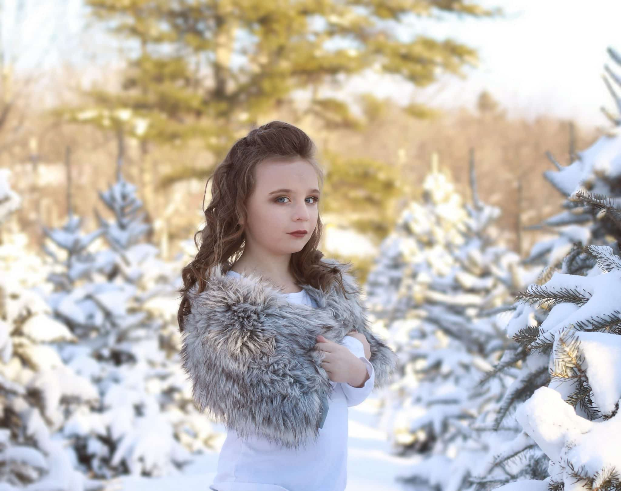 Young girl, white shirt, grey faux fur on her shoulders, curly hair, tree farm, snow covered trees, winter, sideways looking at the camera