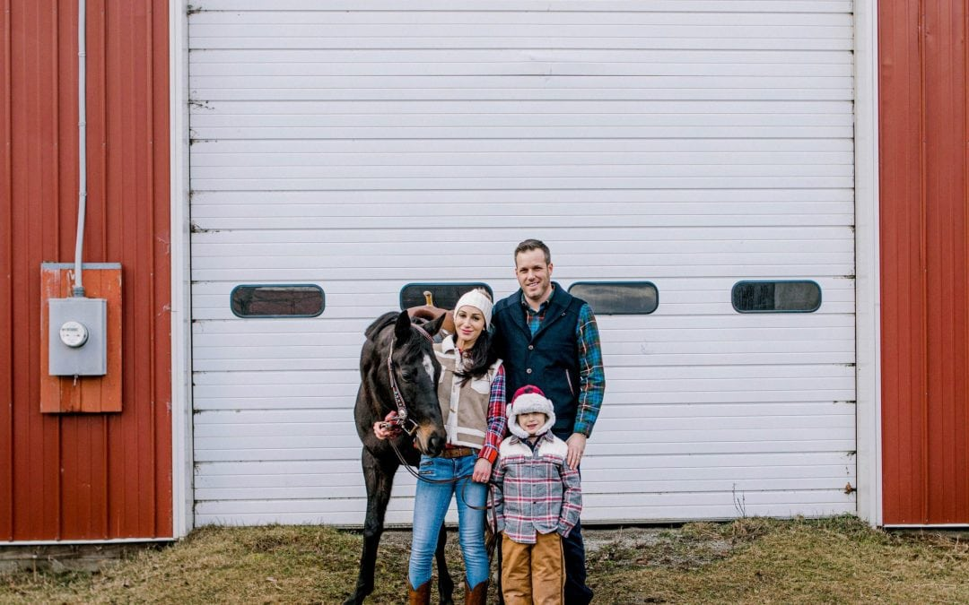 family against a white and red barn looking at the camera for their family photo