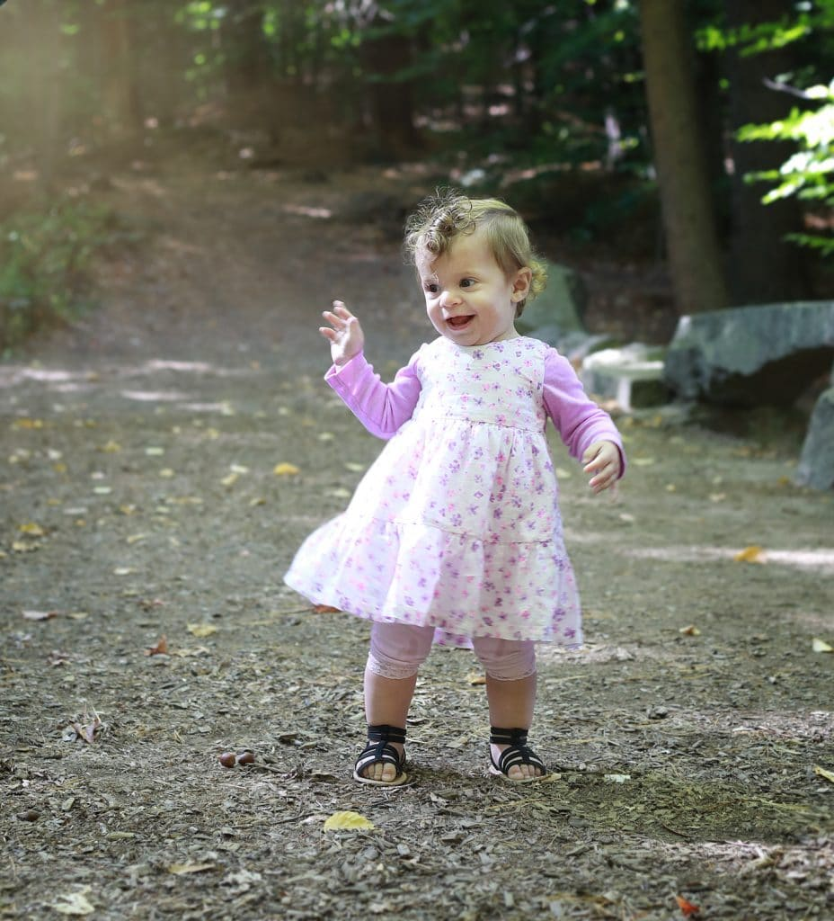 little girl dancing in pink dress on a path in the woods, hands up, curly hair