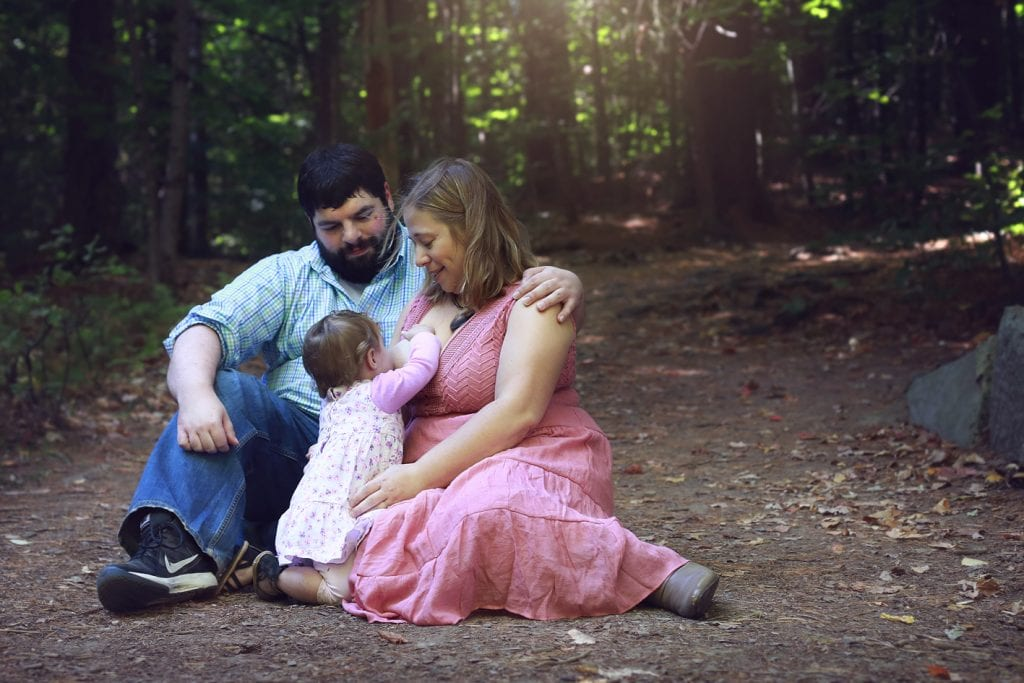 mom in pink dress nursing baby in pink dress, dad in jeans arm around wife in nature