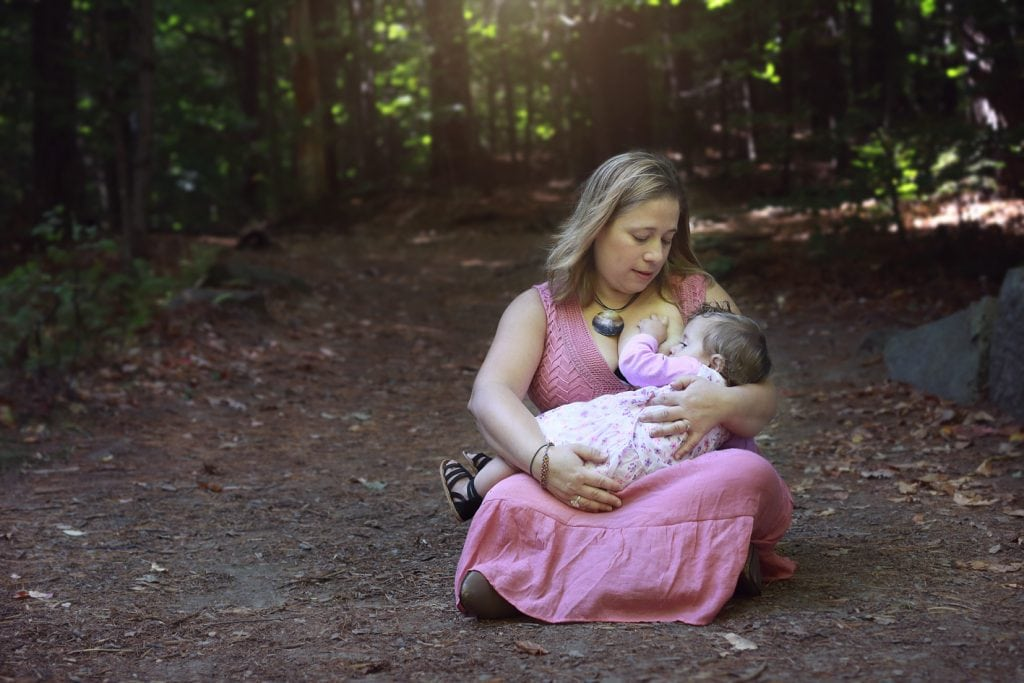 Mom in a pick dress sitting down nursing baby in a pink dress, on a wood path sun coming in above them