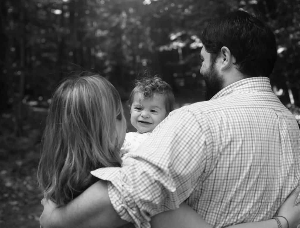 mom and dad back to the camera, baby girl smiling at mom, in black and white