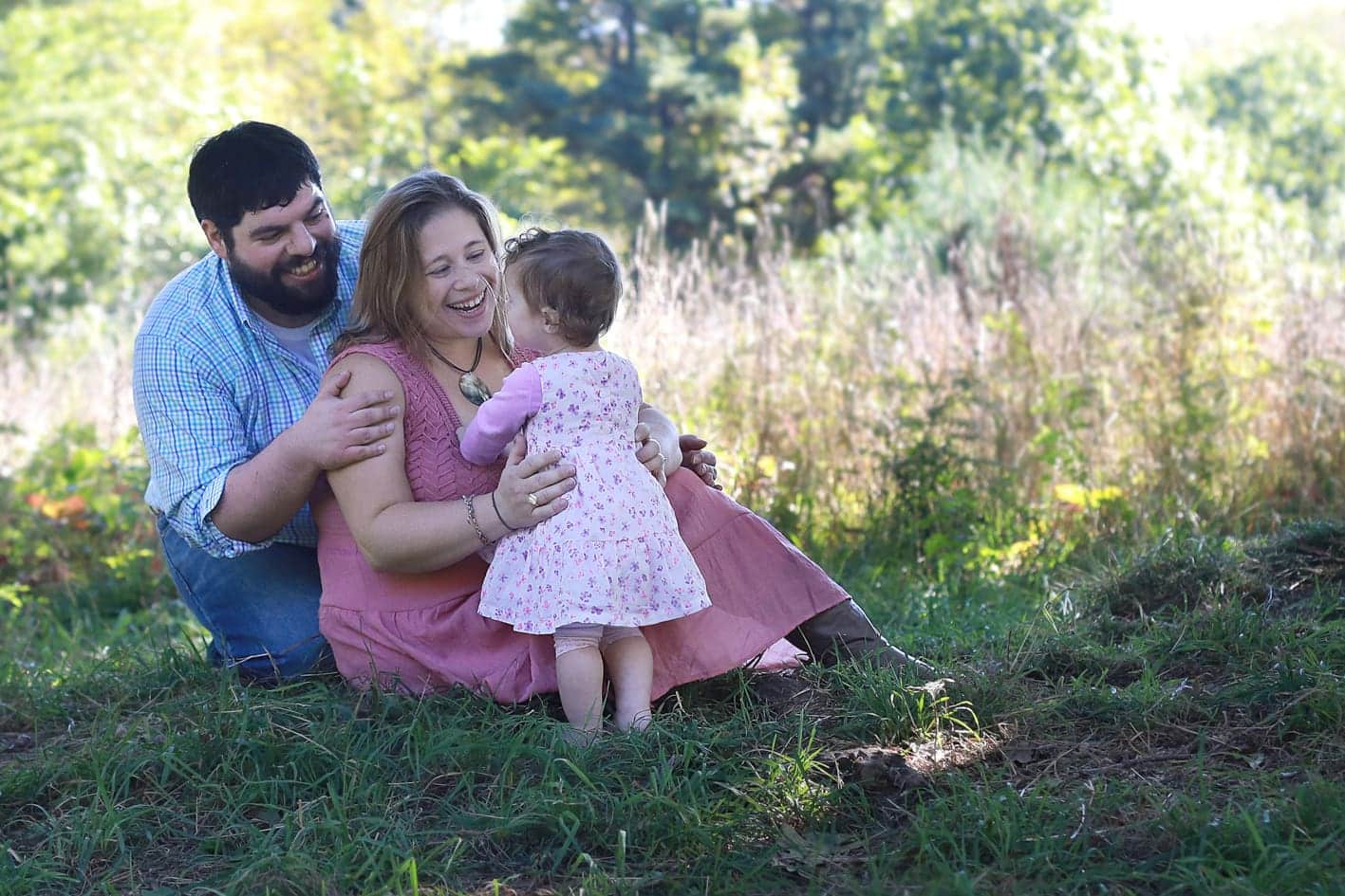 Mom and dad and baby looking at each other in an open field. Mom holding onto toddlers waist