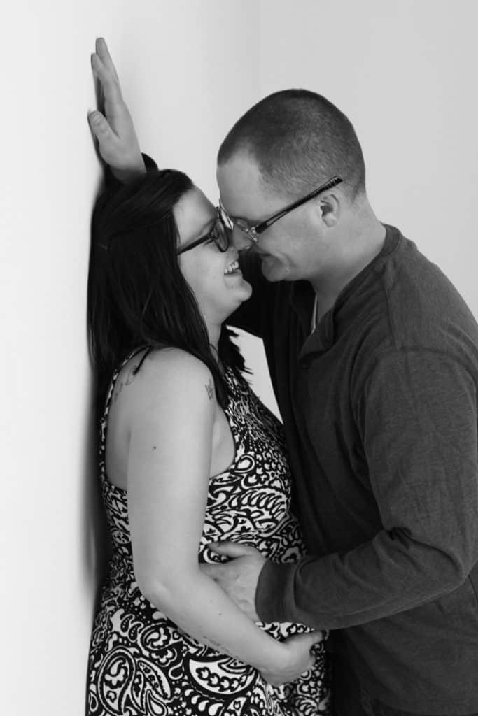 husband and wife, husband almost kissing wife against the wall, hand on her stomach