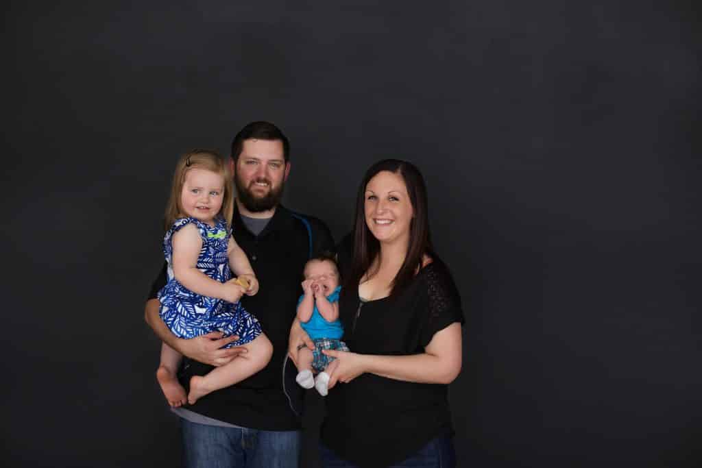 Family photo session. Black background, mom, dad, baby, toddler girl