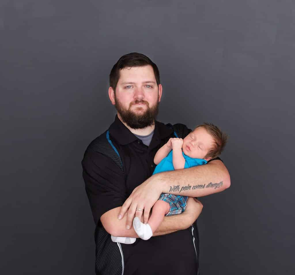 new dad, black background, newborn sleeping