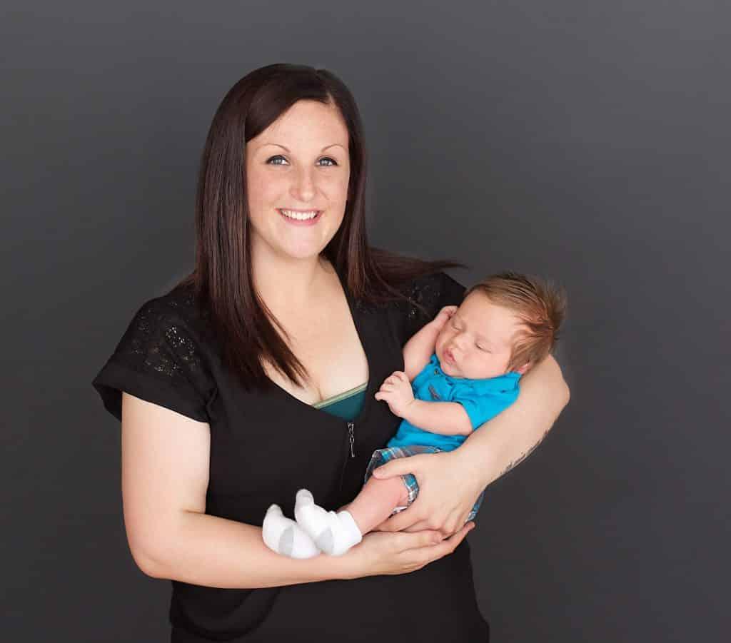 New mom on black backdrop, newborn, sleeping