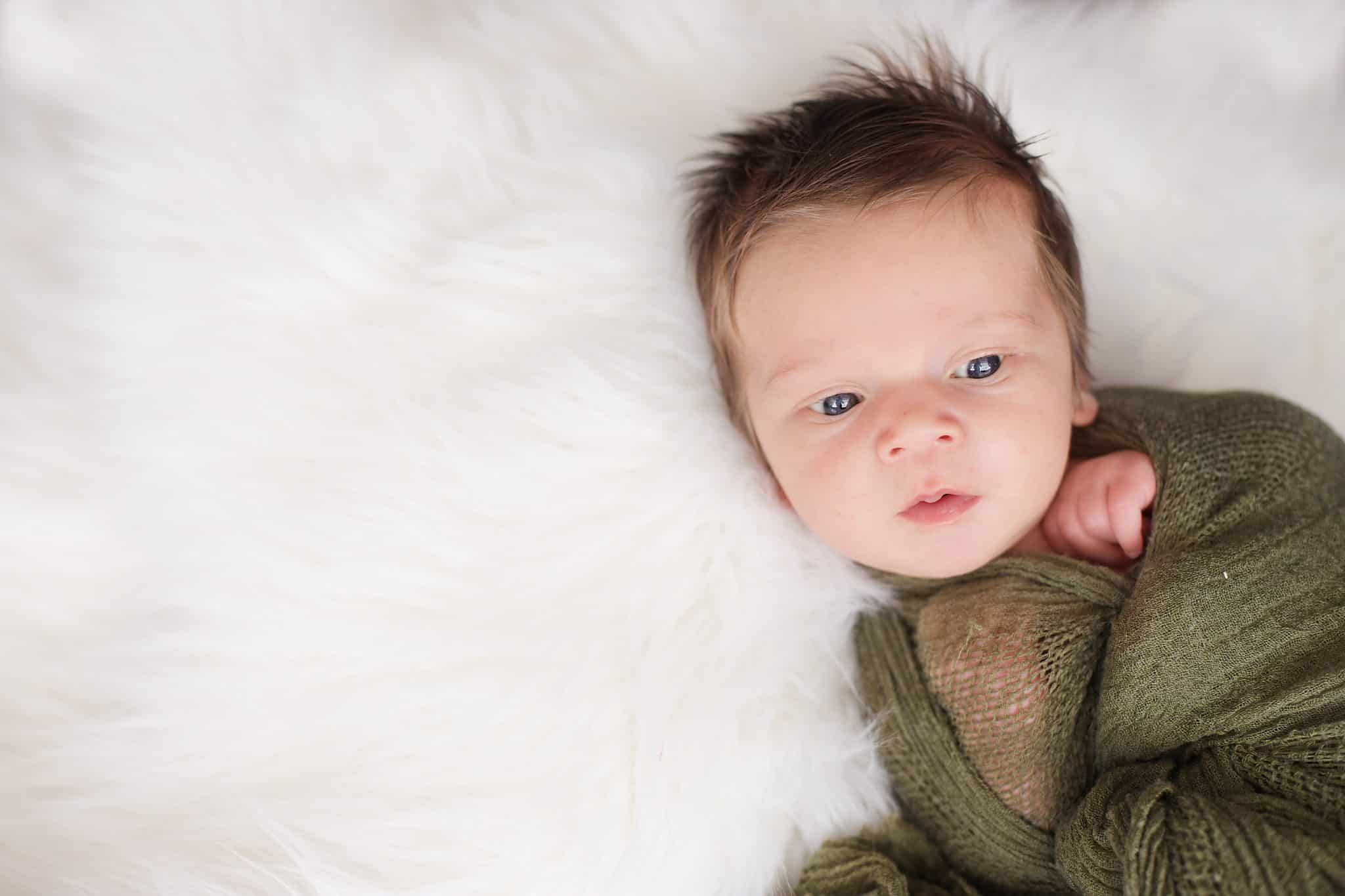 baby boy wide awake wrapped in an olive green wrap on white fur, eyes open