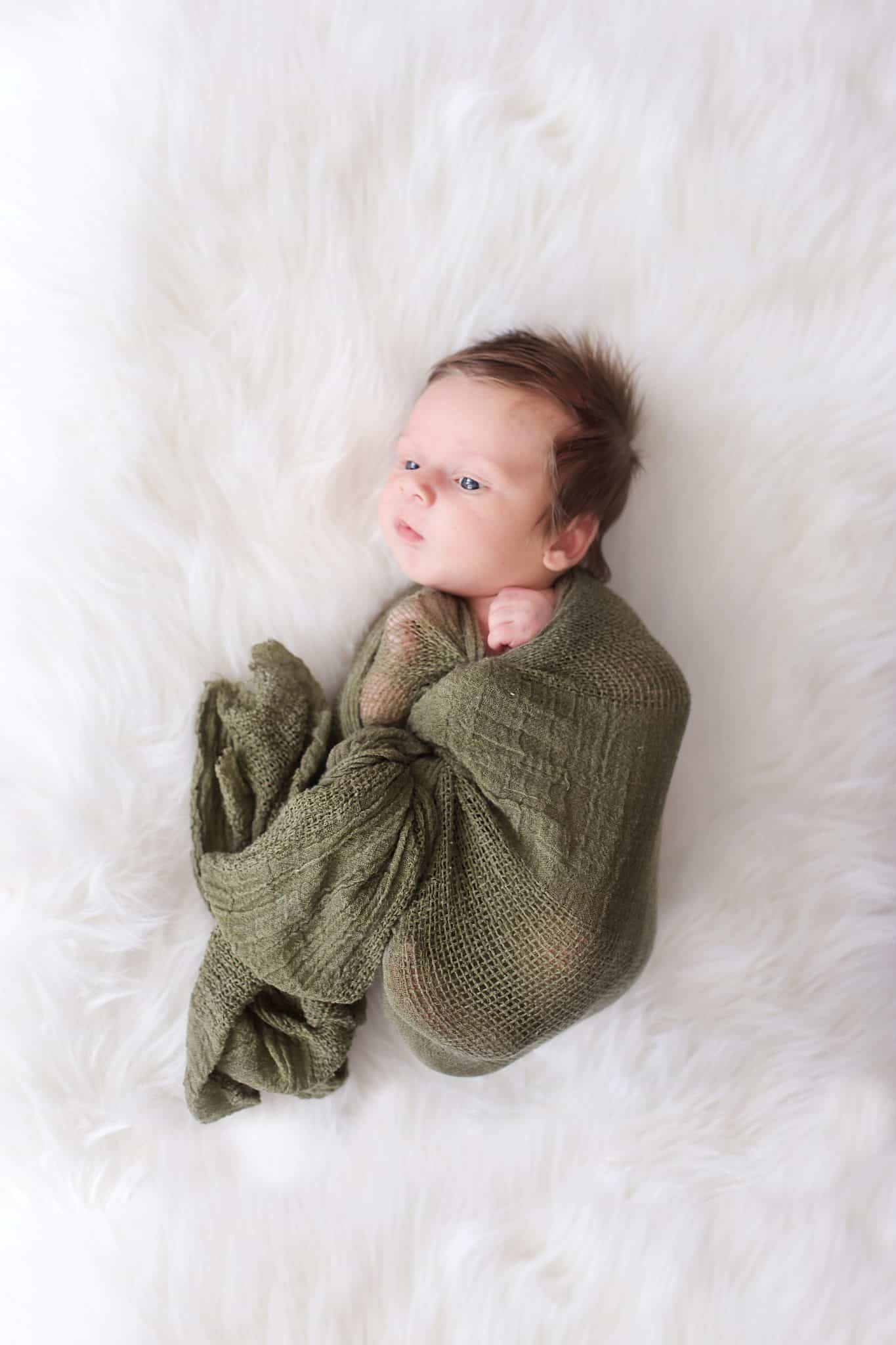 Newborn photo session. Newborn, olive green wrap, white fur blanket, tons of hair, eyes open