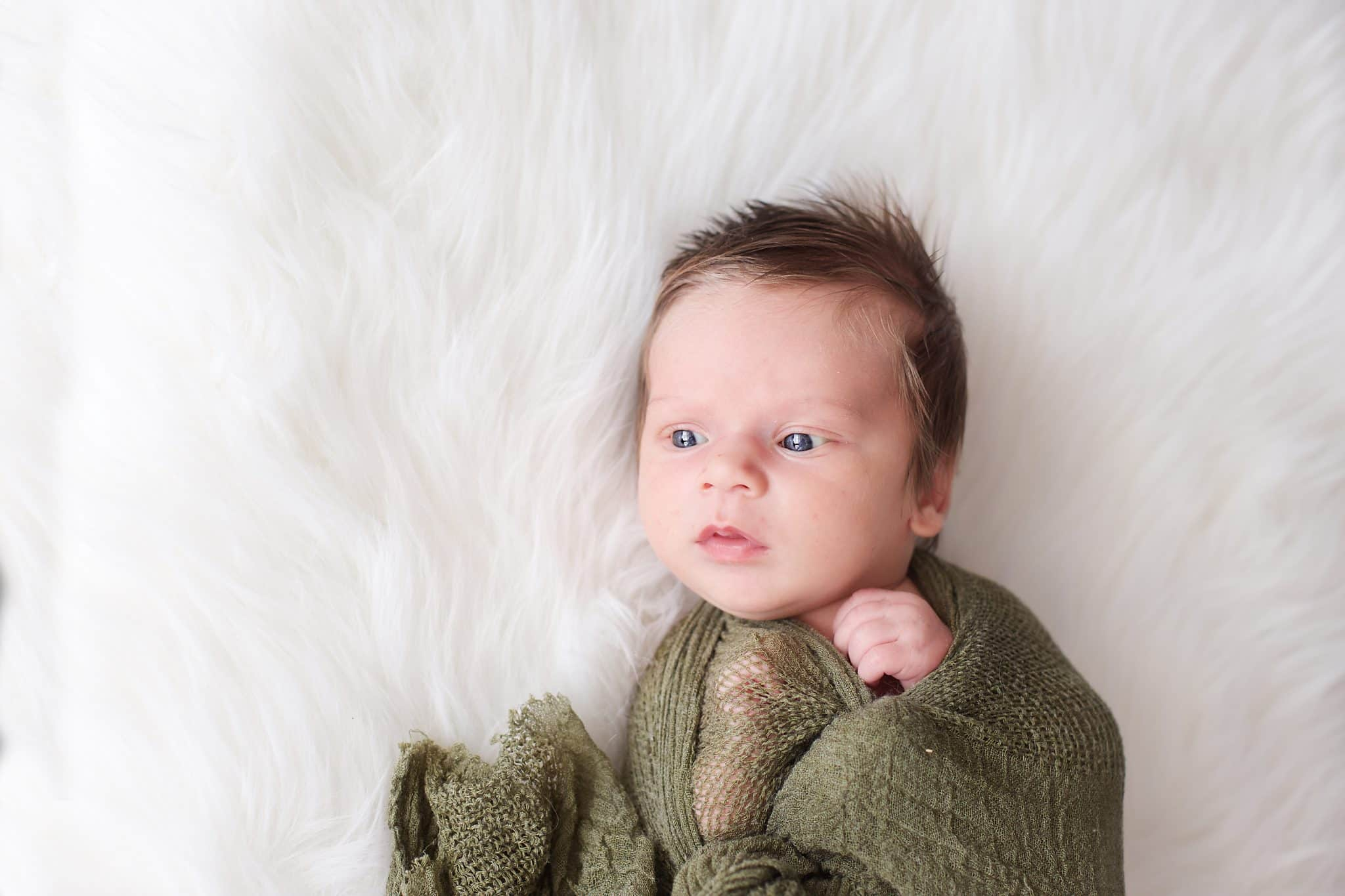 Newborn photo session. Newborn, olive green wrap, tons of hair, eyes wide open, on white fur backdrop