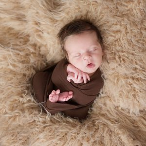 Newborn photo session brown wrap, mouth open, tons of hair, on a tan fur blacket
