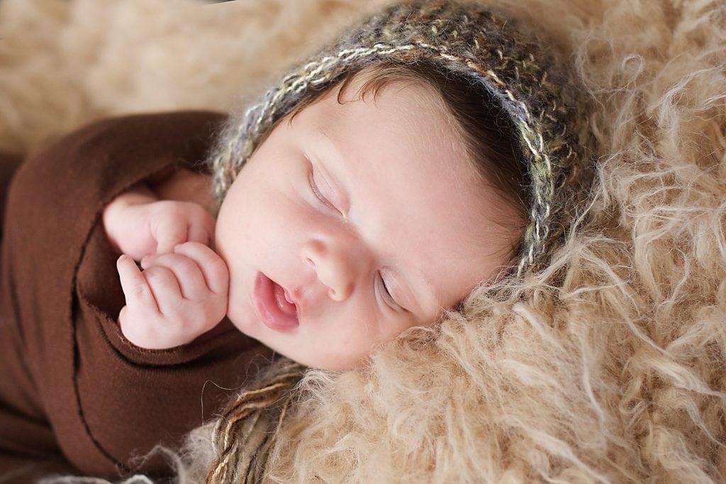newborn in brown wrap, green bonnet, tan fur blanket, sleeping