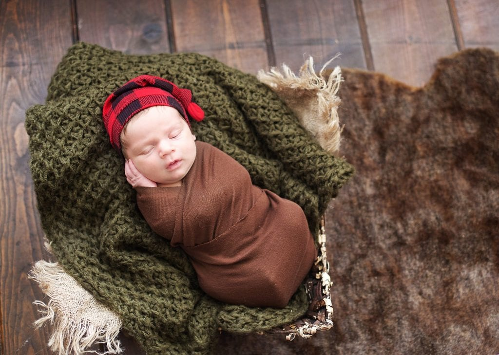 Newborn in brown wrap, burlap, basket, red plaid hat, sleeping