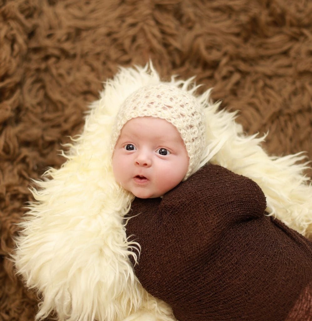 Newborn wrapped in brown, white bonnet, on brown fur