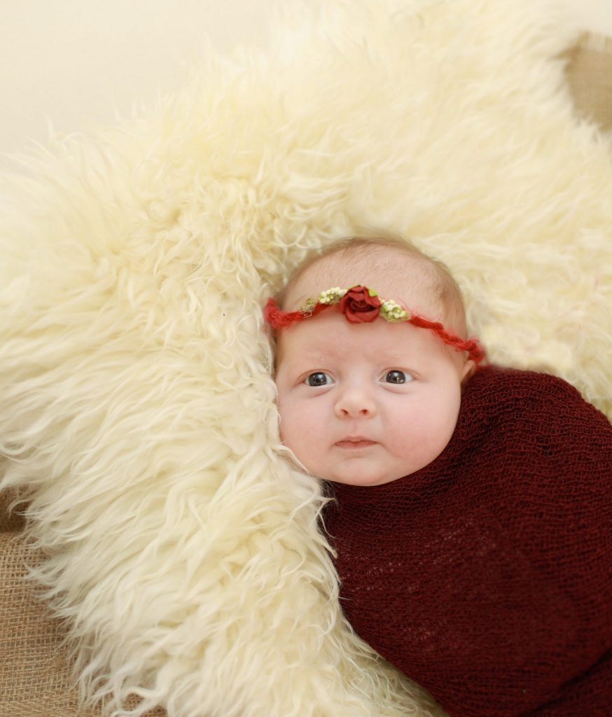 Newborn wrapped in brown, red headband with flower, off white fur
