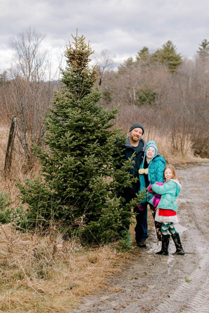 Dad, his girls looking at the camera holding the freshly cut christmas tree
