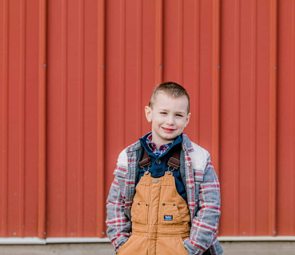 boy looking at the camera against a red barn., dressed in LL Bean clothes
