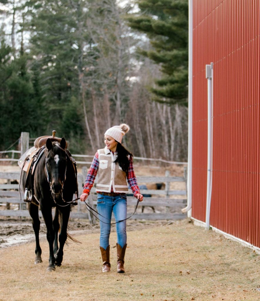 woman looking at the camera with her horse in front of the barn