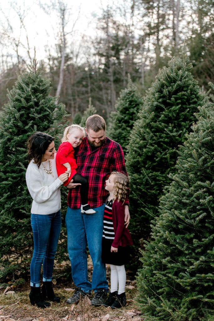 family in red and white at the Christmas tree farm