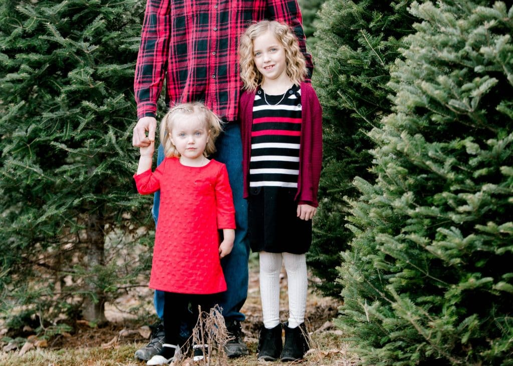 dad, and his two girls at the Christmas tree farm