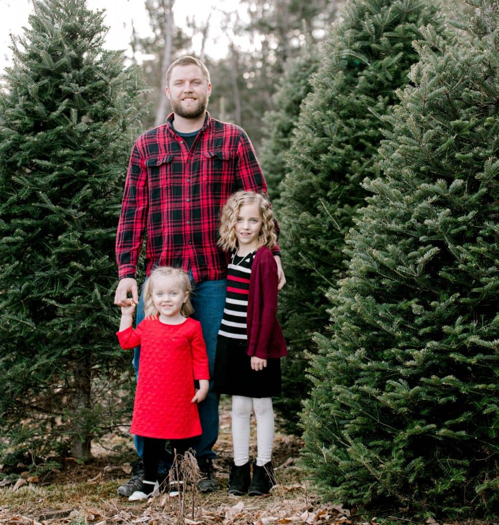 dad and his girls at the christmas tree farm wearing red and white looking at the camera