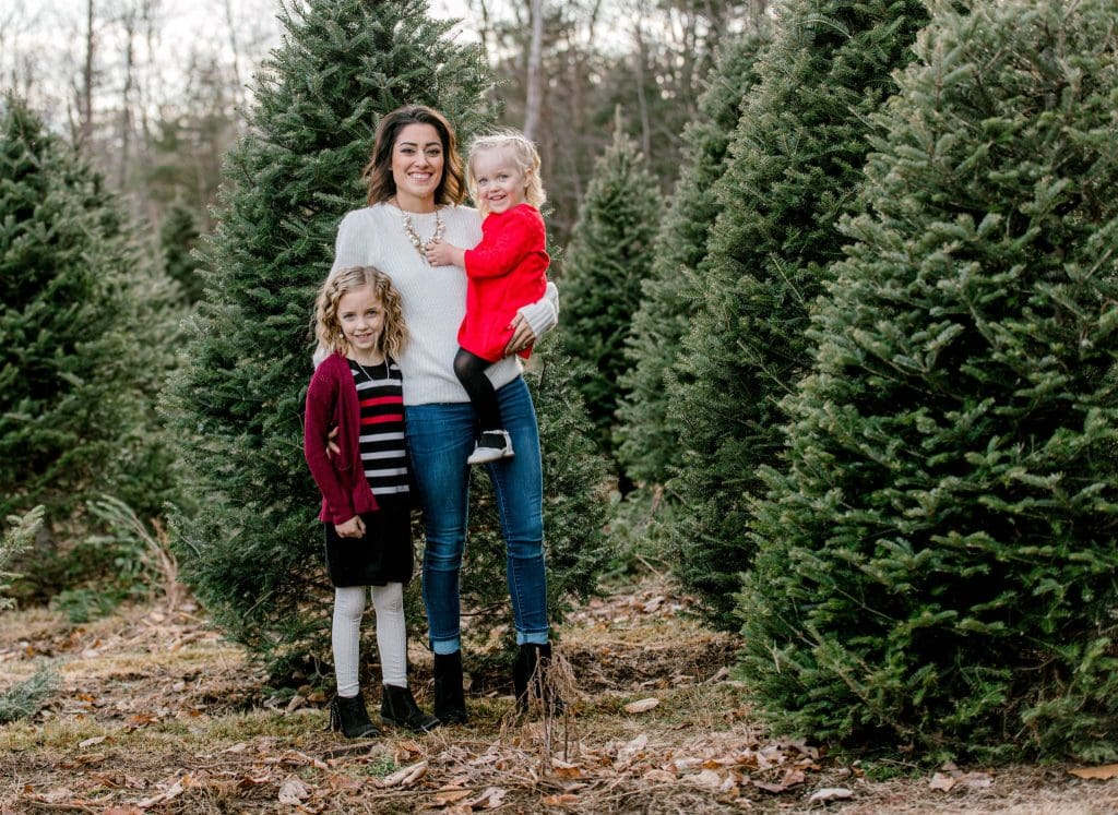mom and girls in the christmas tree farm wearing red and white