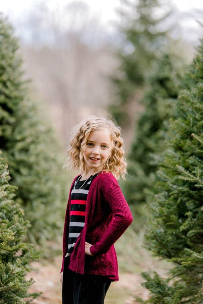 girl standing sideways looking at the camera, hair curled, in a christmas tree farm