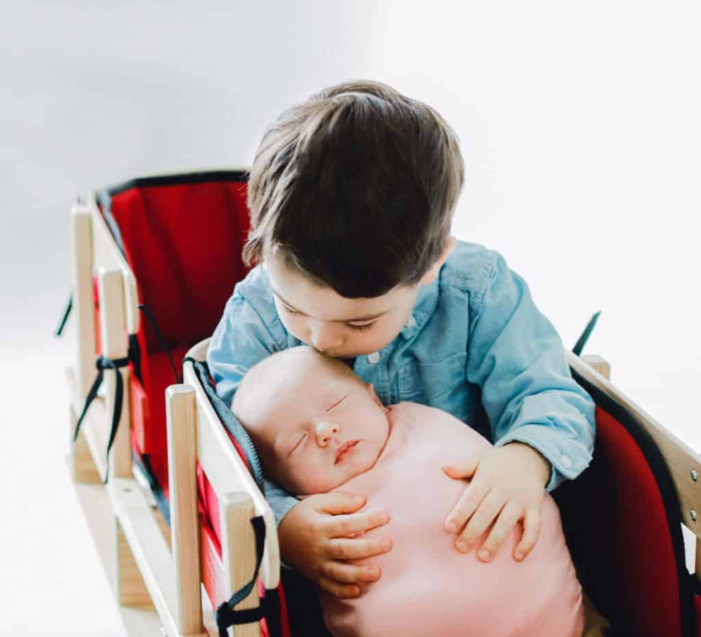 big brother kissing newborn baby girl in a red double sled