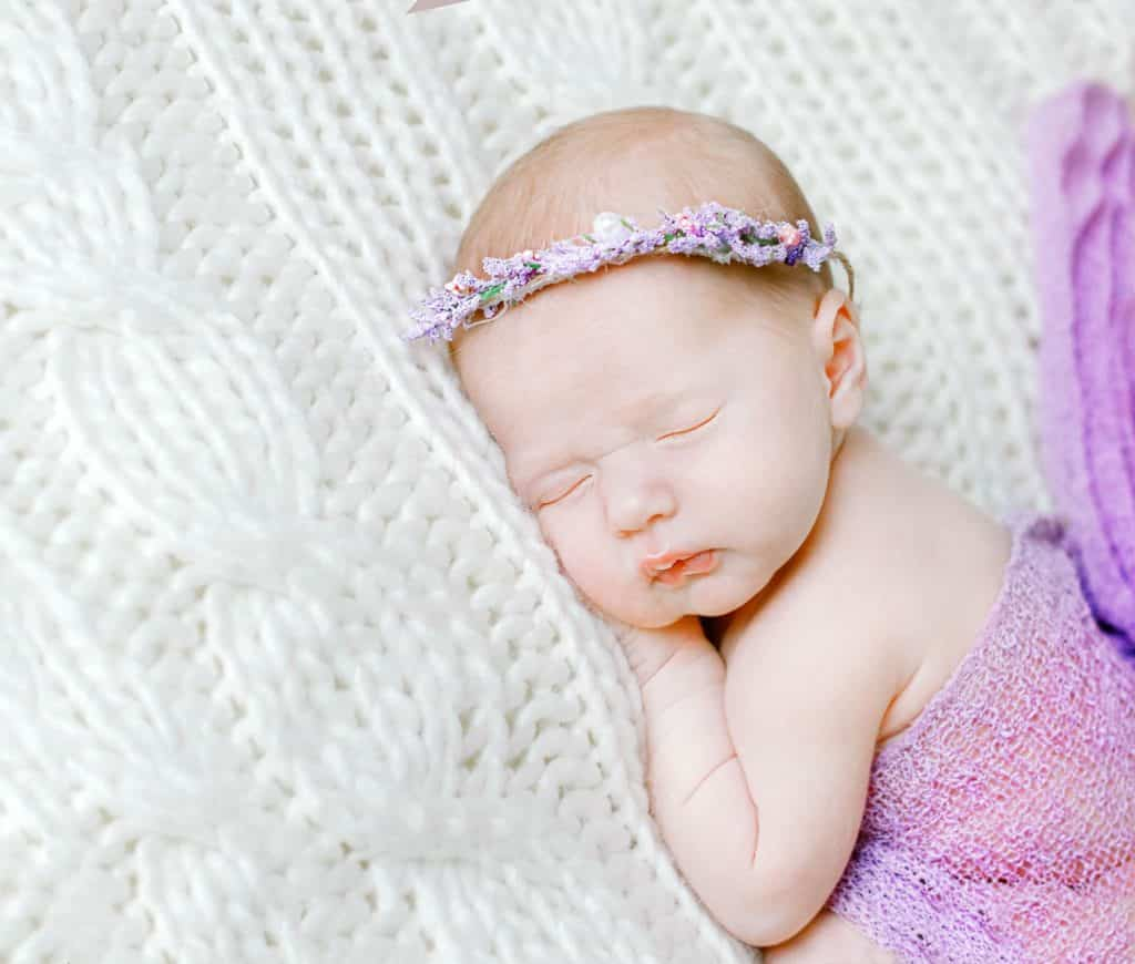 Newborn baby girl laying on her stomach wrapped in lavender with ehr hands under her chin facing the camera