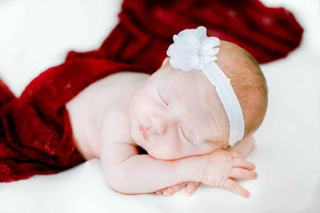 newborn baby girls laying on her stomach with a maroon cover up and a white headband on a white blanket