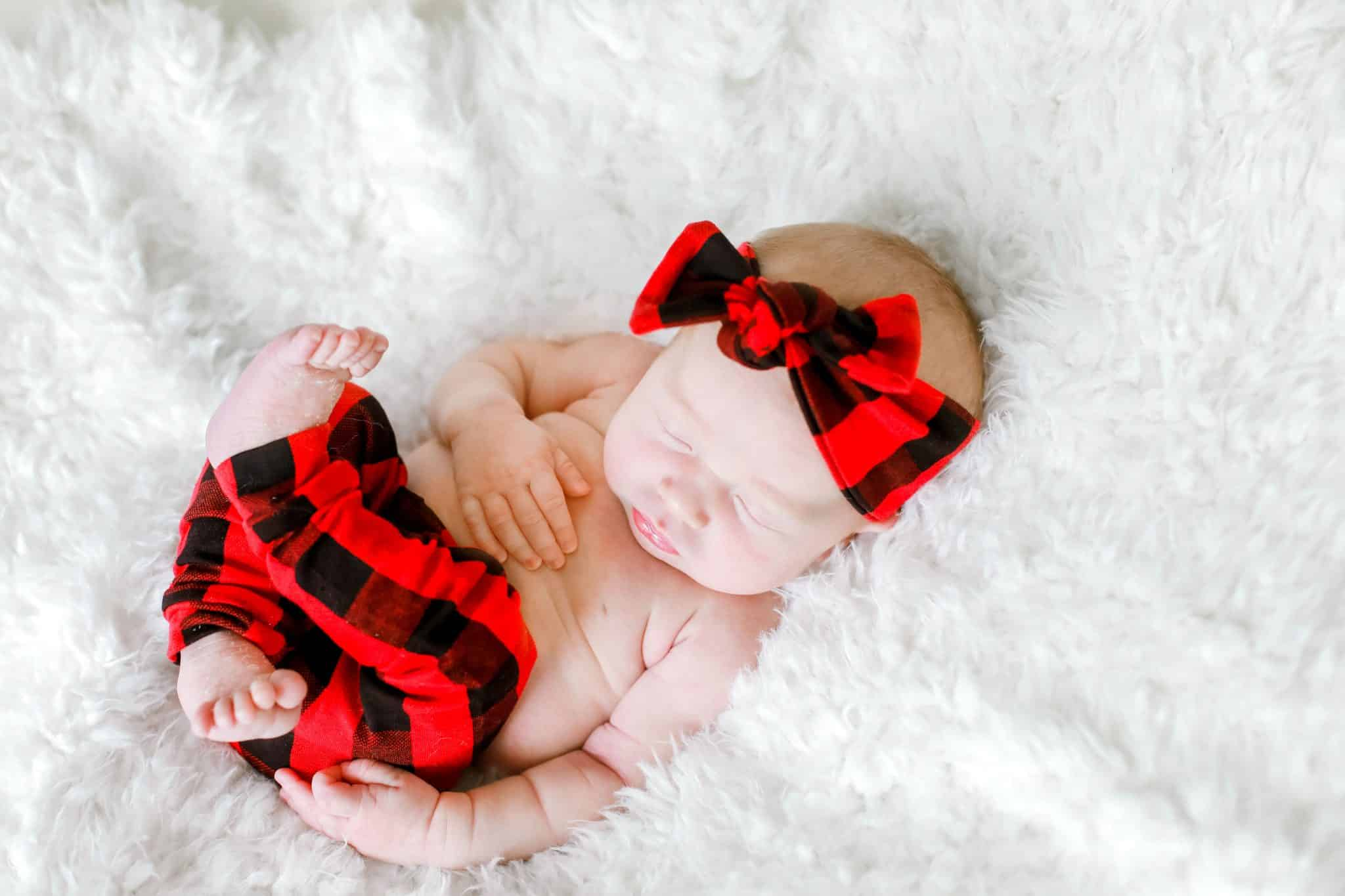 newborn baby laying on her back in red plaid pants and a bow with ehr feet curled up on a white blanket
