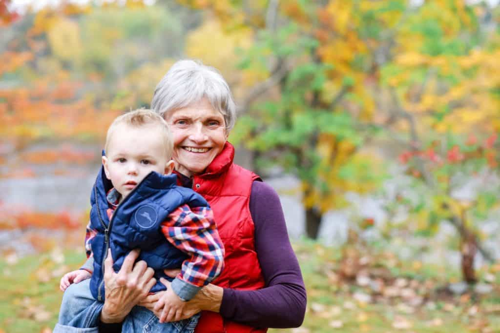 Grandmother with her grandson in the fall looking at the camera