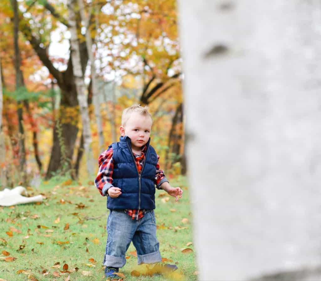 toddler in plaid and a blue vest running around the yard in the fall behind a birch tree