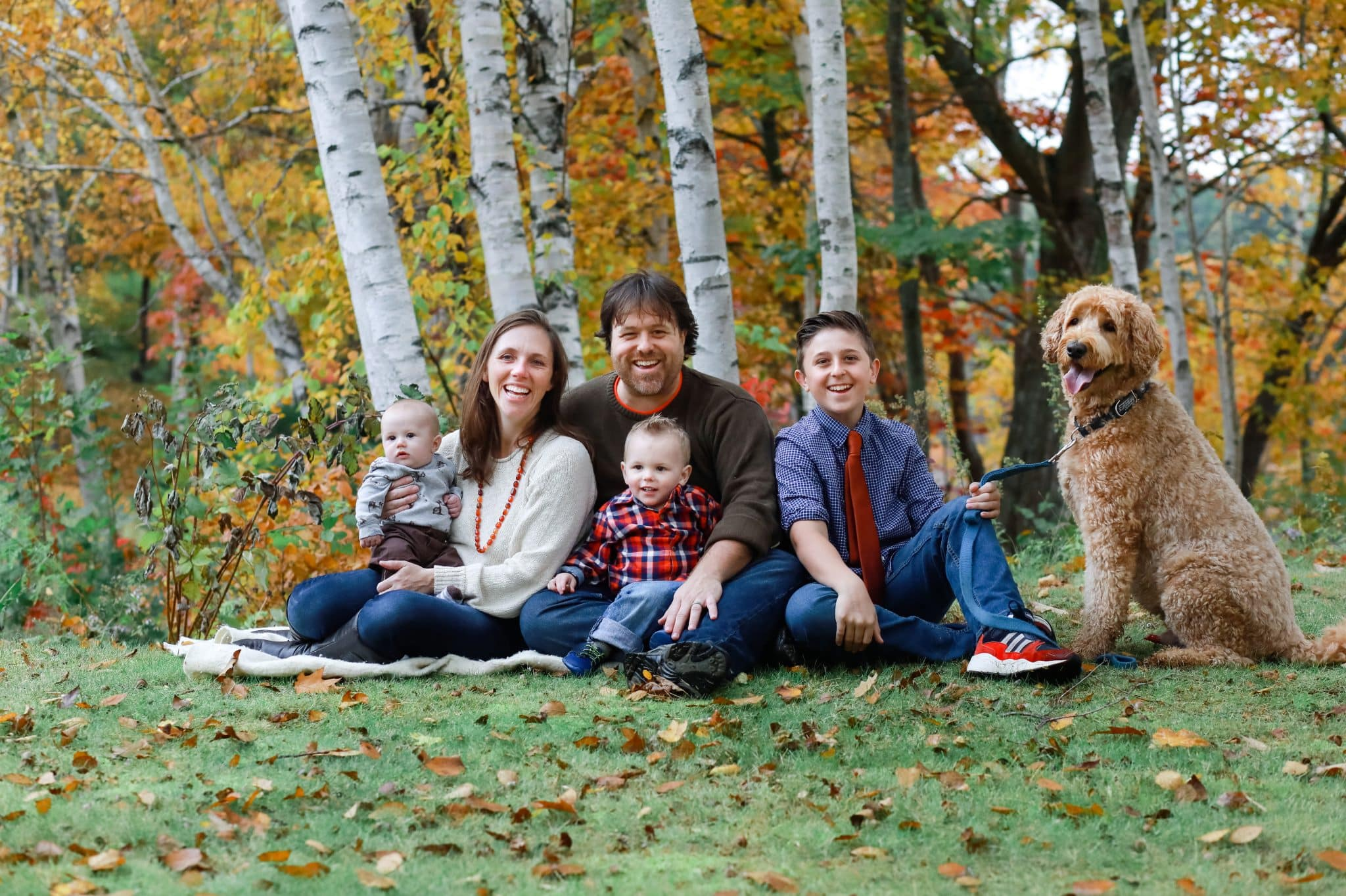 family looking at the photo in the fall with the dog in Bangor Maine