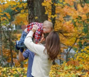mother holder her toddler son up in the air. Fall family photo