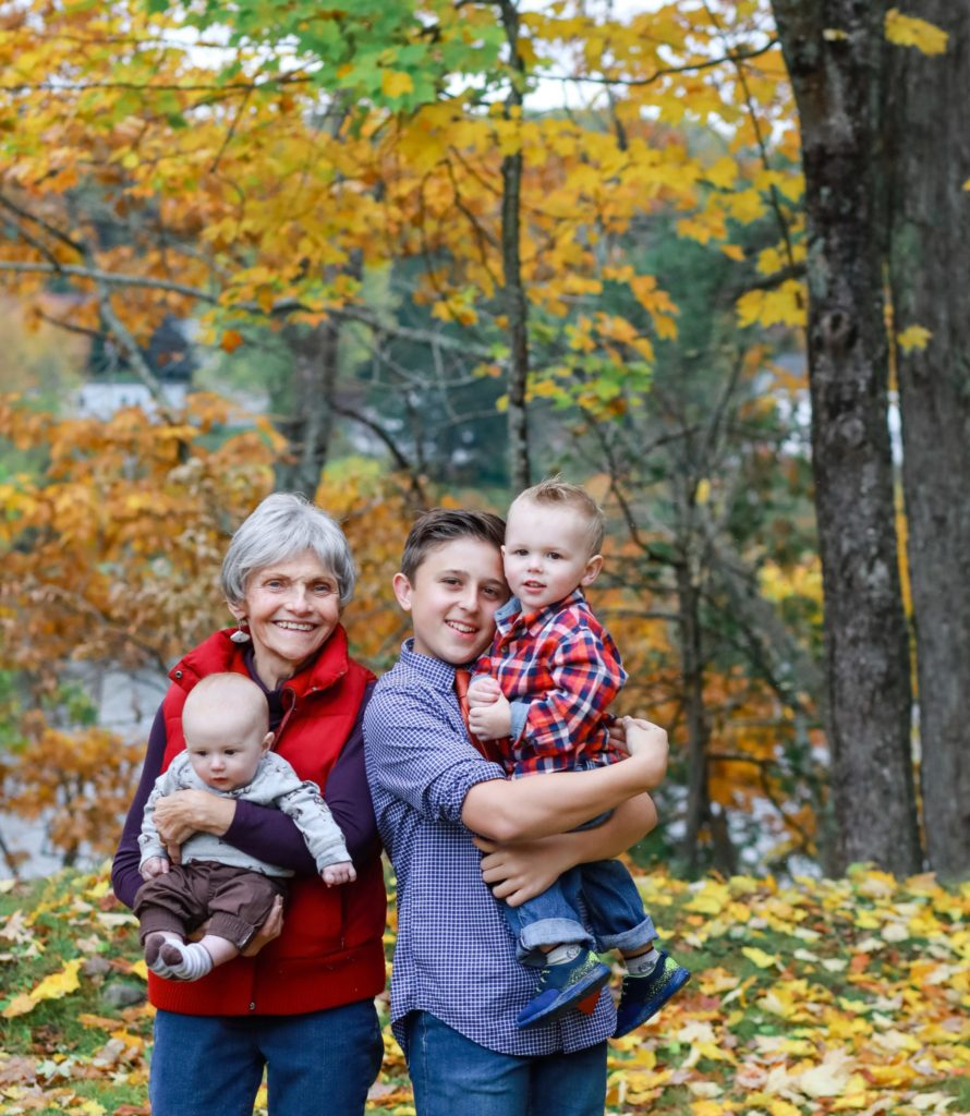 grandmother and all her grandsons in the fall wearing their fall clothes.