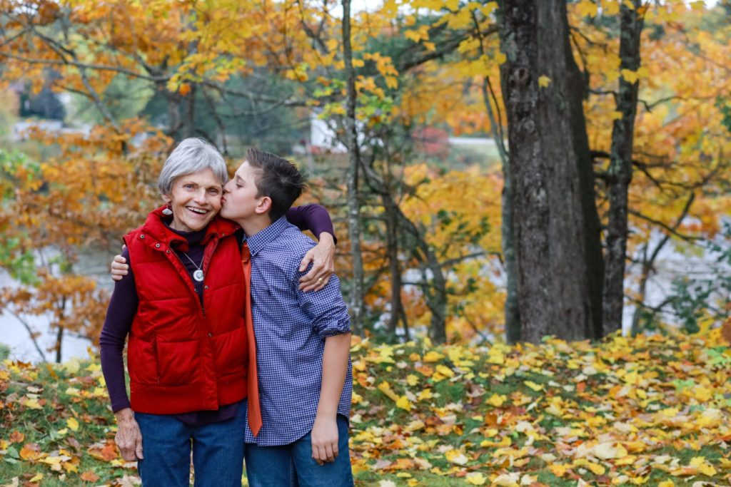 grandmother and her grown grandson kissing her on the cheek in their backyard in the fall. Lifestyle images.